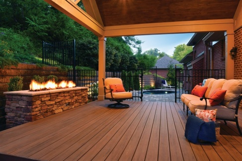 TimberTech Deck leading into a backyard with a firepit fire roaring
